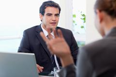 Handsome manager interviewing a female applicant - stock photo