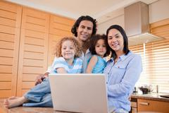Happy family with laptop standing in the kitchen together Stock Photos
