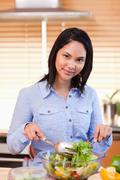 Woman stirring salad in the kitchen - stock photo