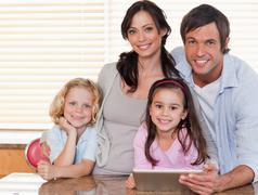 Hymyilevä perhe käyttää tabletti tietokone yhdessä Kuvituskuvat