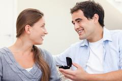 Delighted man proposing marriage to his girlfriend Stock Photos