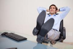 Stock Photo of Smiling businessman leaning back in his chair