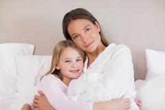 Mother and daughter hugging - stock photo