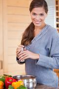 Stock Photo of Smiling woman adding spices to her stew