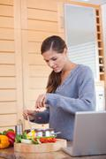 Woman adding carrot pieces to her stew - stock photo
