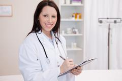 Smiling female physician taking notes - stock photo