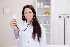 Smiling female doctor using stethoscope - stock photo
