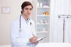 Male doctor with clipboard and pen - stock photo