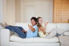 Stock Photo of Couple sitting back to back with a glass of sparkling wine