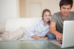Relaxed couple using a laptop - stock photo