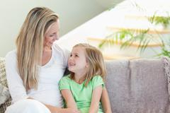 Mother and daughter sitting on sofa - stock photo