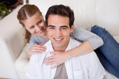Man getting hugged by his girlfriend on the sofa - stock photo