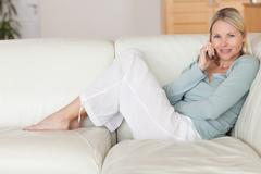 Woman sitting on the couch listening to caller Stock Photos