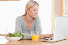 Woman having healthy lunch while working on her laptop - stock photo