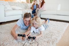 Isä ja poika videopelien pelaamiseen Kuvituskuvat