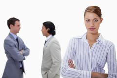 Stock Photo of Businesswoman with talking colleagues behind her
