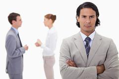 Serious businessman with talking colleagues behind him - stock photo