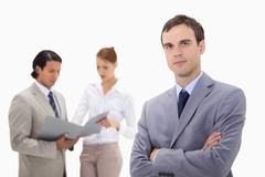 Young businessman with talking colleagues behind him Stock Photos