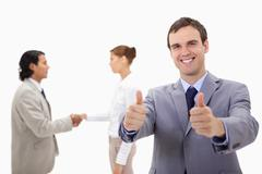 Stock Photo of Businessman approving with hand shaking colleagues behind him