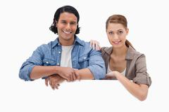 Couple leaning on blank wall - stock photo