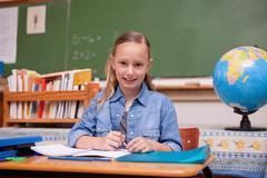 Stock Photo of Cute schoolgirl doing classwork