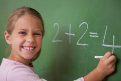 Happy schoolgirl writing a number - stock photo