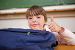 Stock Photo of Schoolgirl posing with a bag and the thumb up