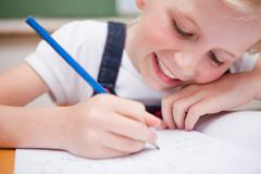 Stock Photo of Close up of a schoolgirl writing something