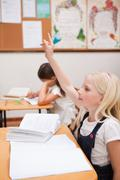 Portrait of a pupil raising her hand Stock Photos
