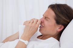 Side view of sneezing woman Stock Photos