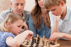 Stock Photo of Focused siblings playing chess in front of their parents