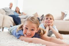 Siblings lying on a carpet Stock Photos