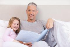 Smiling father reading a story to his daughter - stock photo