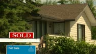 Real estate sold sign and house, average suburban home Stock Footage