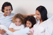 Stock Photo of Happy family enjoys reading a story together