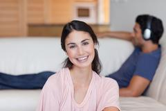 Woman posing while her fiance is listening to music Stock Photos