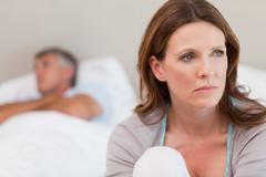Sad woman on bed with her husband in the background - stock photo
