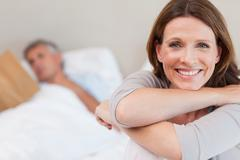 Smiling woman on bed with reading husband in the background Stock Photos