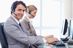 Smiling operators using a computer - stock photo