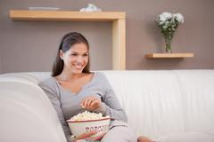 Smiling woman having popcorn while watching a movie - stock photo