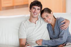 Happy couple enjoying their time together on the couch - stock photo