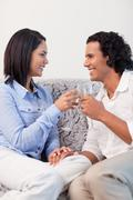 Stock Photo of Couple drinking sparkling wine on the sofa
