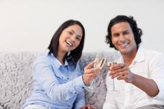 Stock Photo of Couple celebrating with sparkling wine on the couch