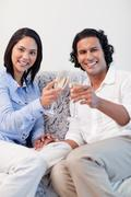 Stock Photo of Happy couple drinking sparkling wine on the sofa