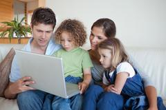 Serene family using a notebook - stock photo