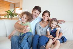 Happy family watching TV together Stock Photos