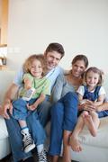 Muotokuva onnellinen perhe television katselun yhdessä Kuvituskuvat