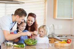 Family preparing salad together Stock Photos