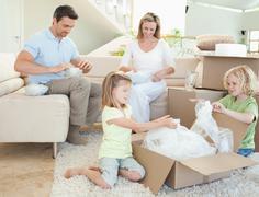 Family unpacking cardboard box - stock photo