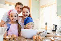 Stock Photo of Cheerful family preparing dough